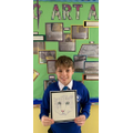 A Year 6 pupil proudly shows us his amazing artwork