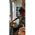 Mete helping to cook breaded chicken for dinner.