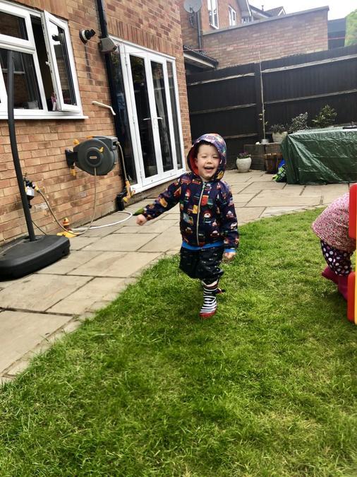 Joshua ran round his toys in the garden.