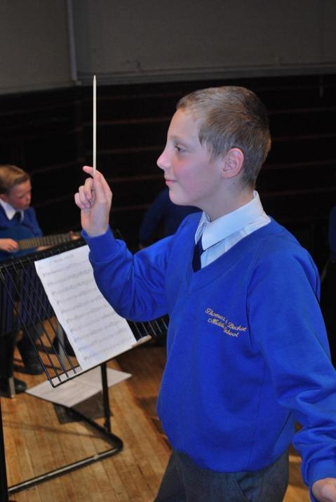 Photo pf pupil conducting the orchestra