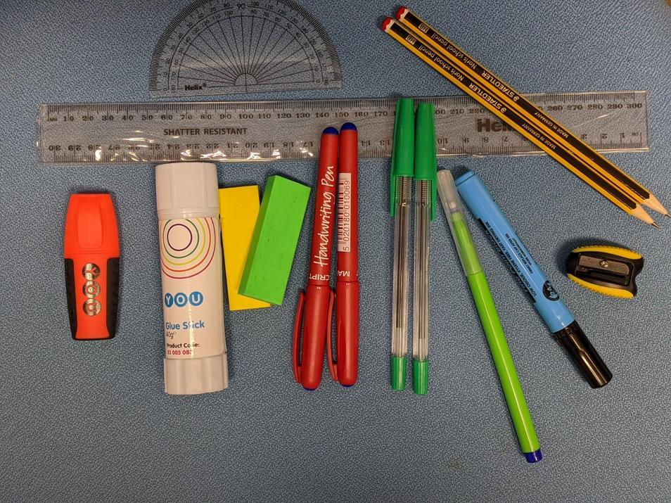 Photo of 2 pens, 2 pencils, a whiteboard pen, 2 green pens, a sharpener, 2 rubbers, a ruler, a highlighter, a glue stick, a protractor and a pen