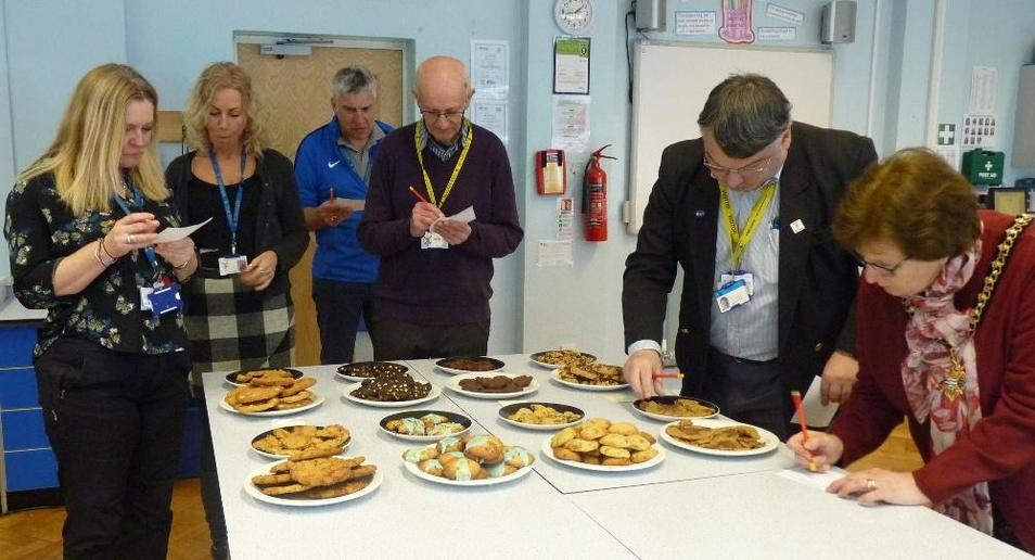 Photo showing staff and visitors judging the baking competition