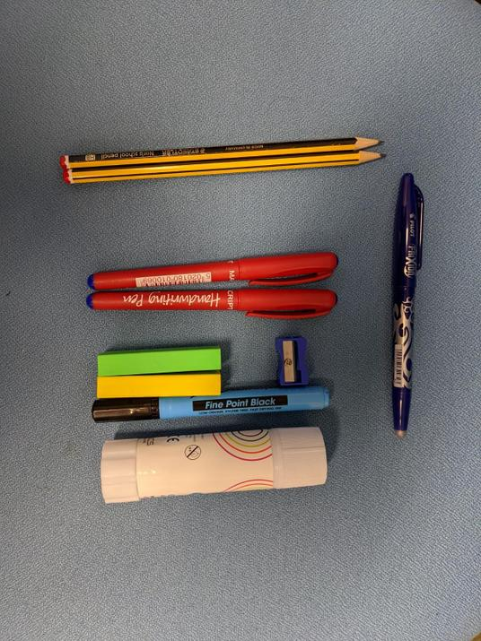 Photo of a Pilot frixion rub out pen, a glue stick, 2 pens, 2 rubbers, a whiteboard pen, 2 pencils and a sharpener