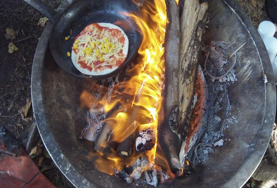 Photo of pizza cooking on the firepit
