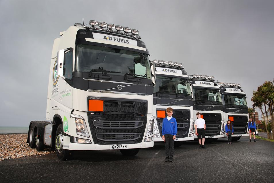 Picture of lorries with pupils in front