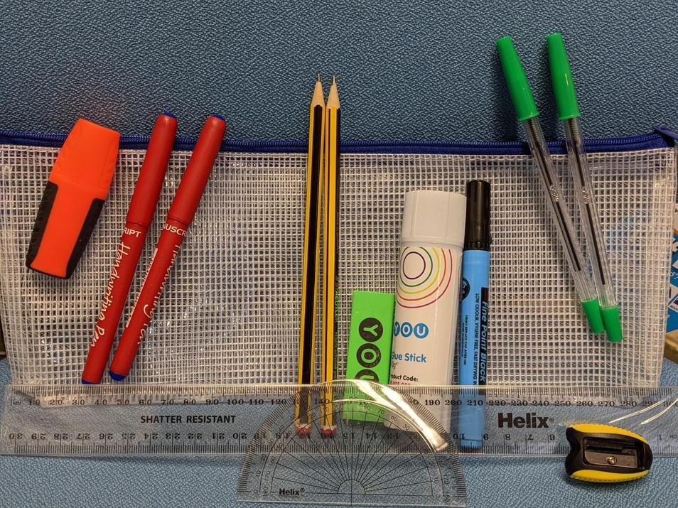 Photograph of 2 pens, 2 pencils, 1 whiteboard pen, 2 green pens, a sharpener, a rubber, a ruler, a highlighter, a glue stick, a protractor and a pencil case