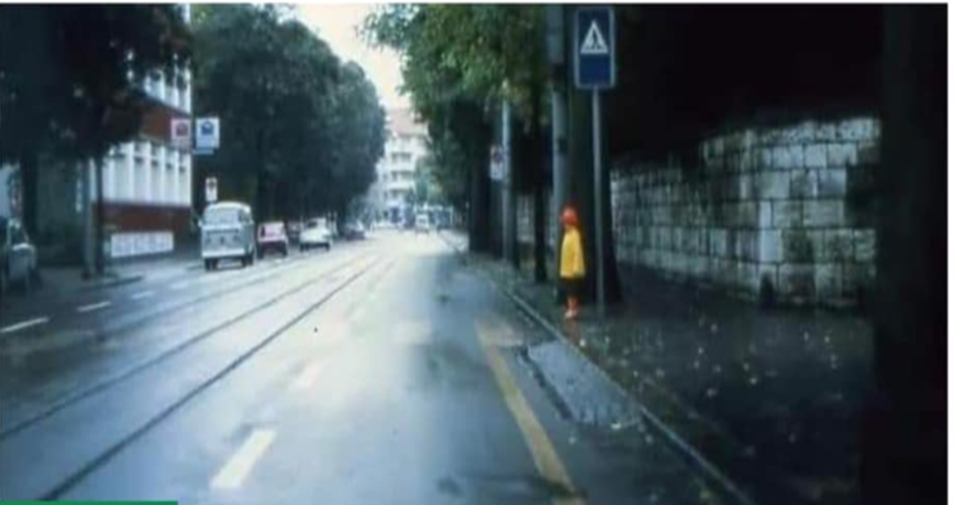 Photo of child wearing bright coloured clothing standing at the side of the road