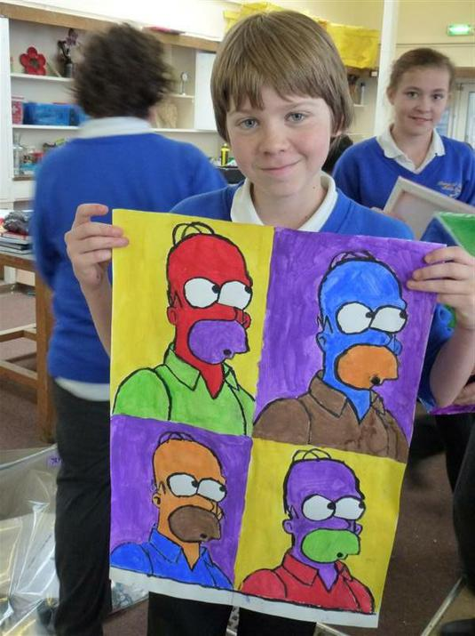Photo of pupil holding artwork