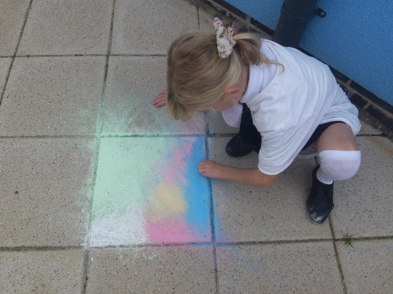 Photo of pupil using chalk outside