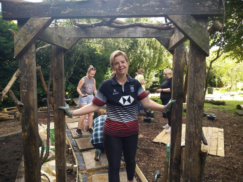 Miss Arnott standing underneath the arch she built using donated scrap wood