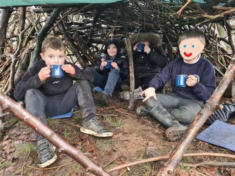The children enjoying hot chocolate in their den