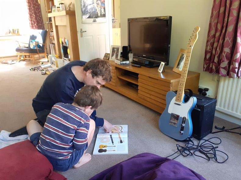Learning about the guitar with dad.