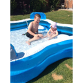 Charlie T and Emmy playing in the paddling pool