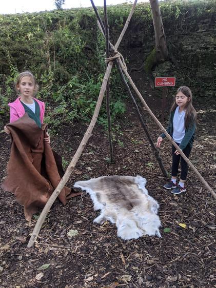 Shelter building using wood and pelts.