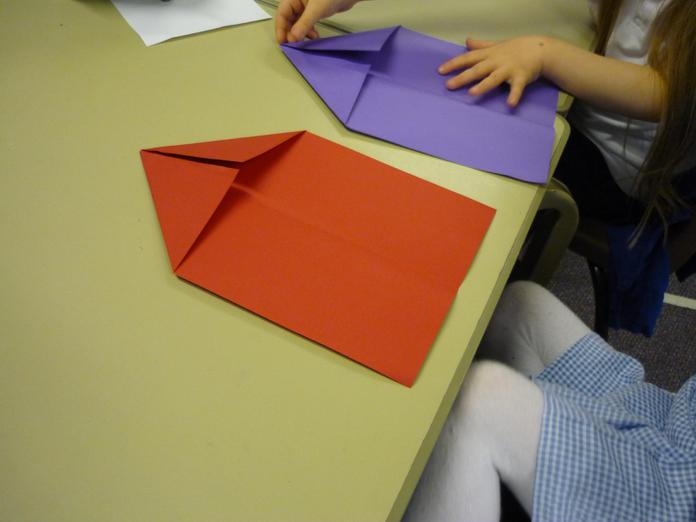 2. Fold the top corners into the centre.