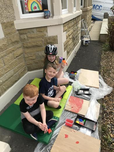 Siblings enjoying painting outside.