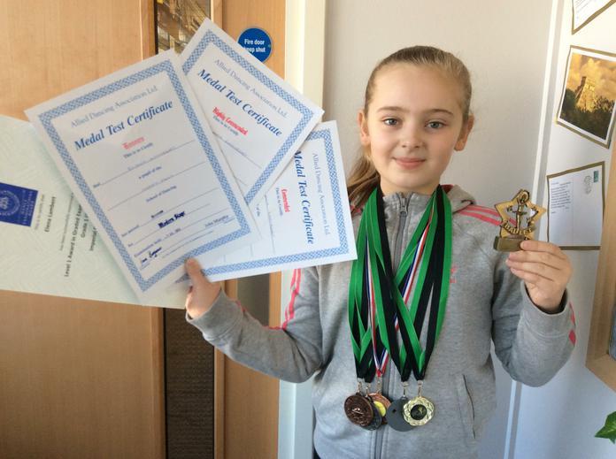 Elena has lots of medals for gymnastics.
