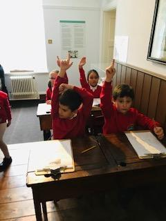 Pretending to be school children of 100 years ago.