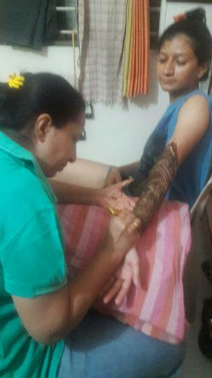 Applying henna to Gauri's arms.