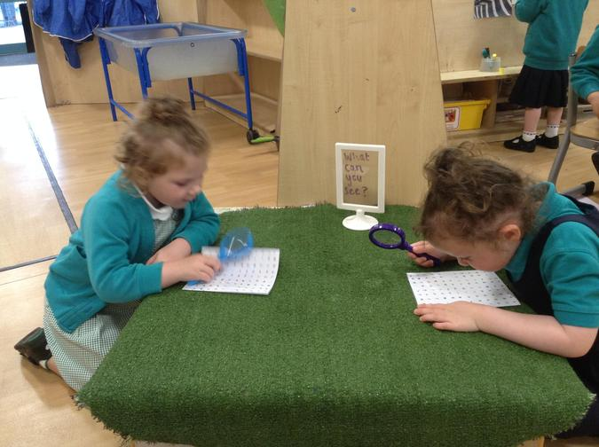 Using magnifying glasses to read really tiny words!