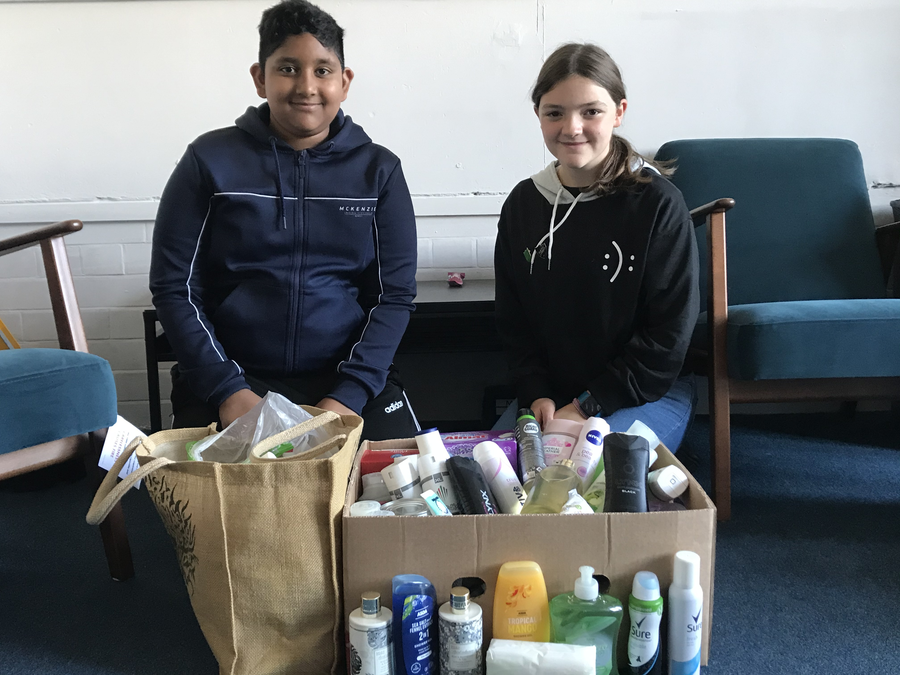Head boy & Head girl with a selection of our Harvest donations for the local foodbank