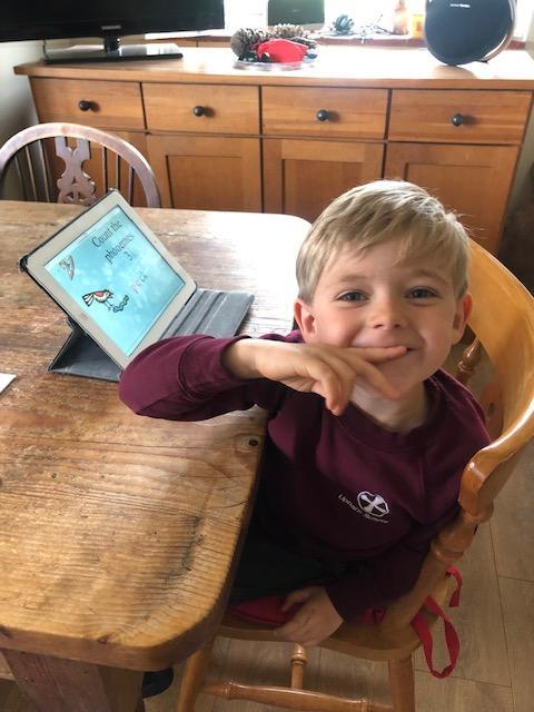 Learning at home in his school uniform!
