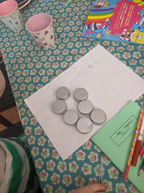 Etta has used tins to add and subtract.