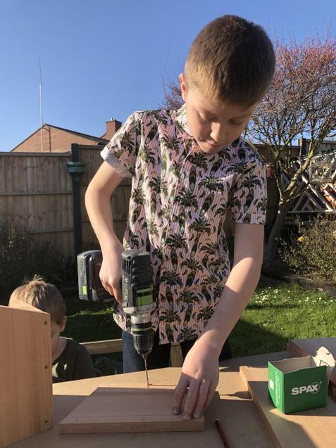 Harrison making bird boxes.
