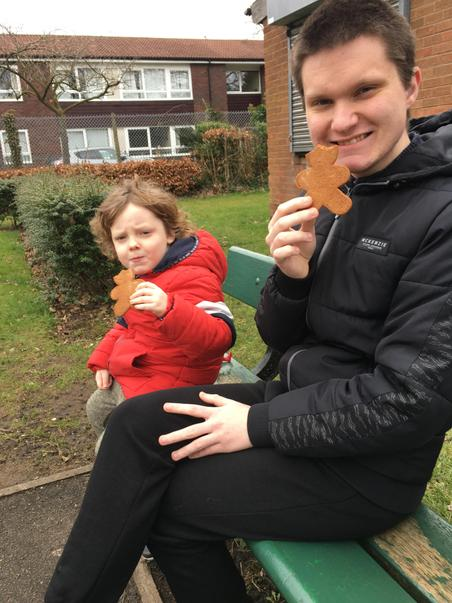 Nathan eating gingerbread with his big brother