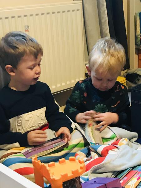 Alfie reading books with his brother