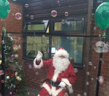 Father Christmas waving at the children.