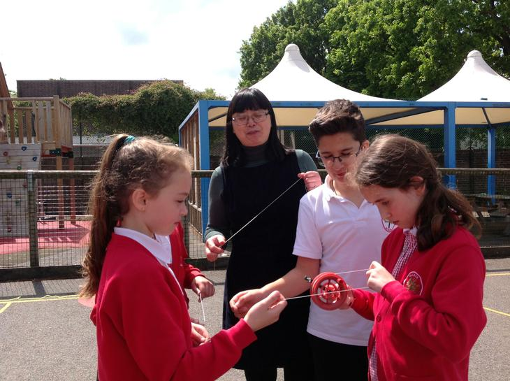 Mrs LI showing the children how to fly a kite.