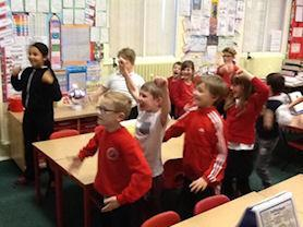 Oak Class using their bodies to find the pitch and rhythm of a piece of music.