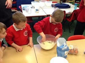 Reception children taking it in turns to stir the mixture.