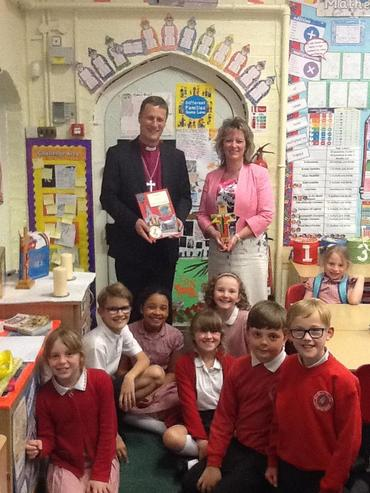 Bishop Martyn receiving a special card from Mrs Hopkins and the children