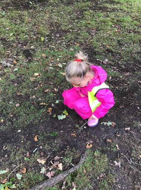Exploring the mud – writing her name with a stick.