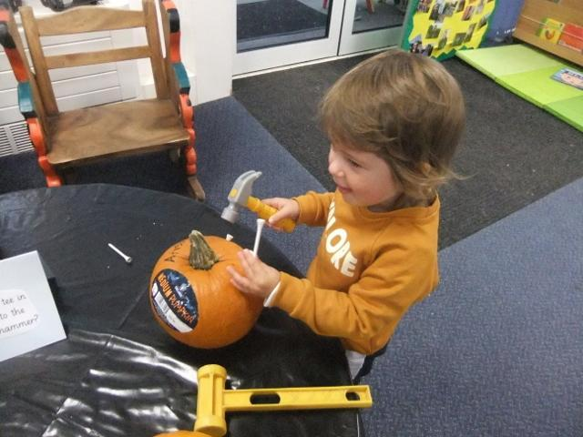 Hammering gold tees into our pumpkins