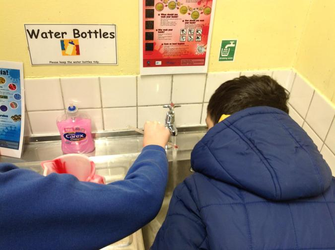Ummar and Dylan measuring the temperature of hot water from the tap