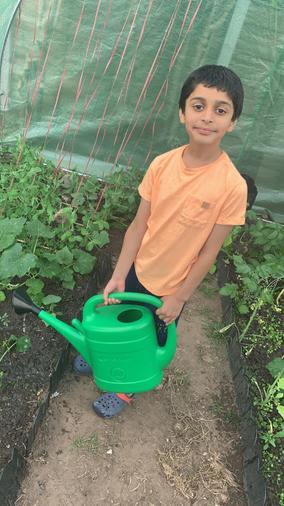 Adam watering his homegrown vegetables