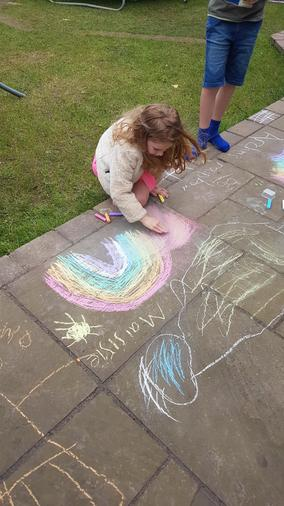 Maisie drawing rainbows for the NHS