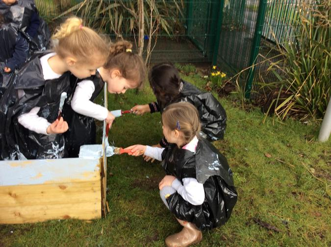 Painting our raised bed using teamwork.