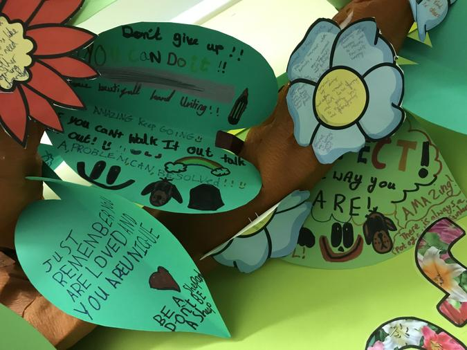 Y6 have written well-being messages on the larger leaves of the tree