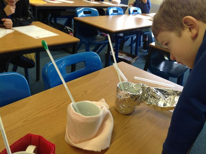 Nico is checking the temperature of the cup wrapped in foil