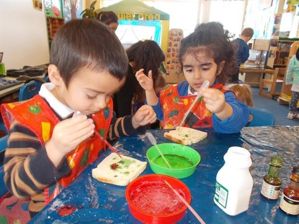 Painting bread with food colouring.