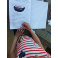 Maya writing her recipe in her book.