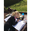 Lizzie enjoying writing about her bug hunt.