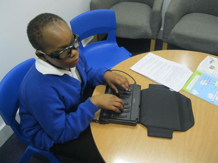 Using a Braille Note Touch to record work.