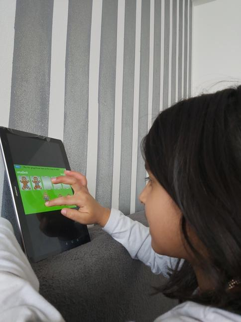 Inayah completing activities on her ipad
