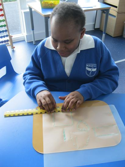 Using a tactile ruler to draw and measure lines.