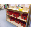 Labelled boxes help the children when tidying.